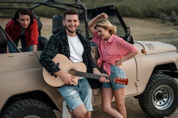 Счастливые друзья играют на гитаре во время путешествия на машине