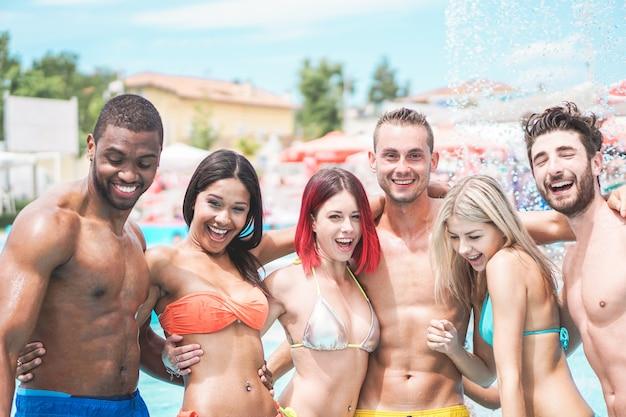 Счастливые друзья играют в вечеринку у бассейна