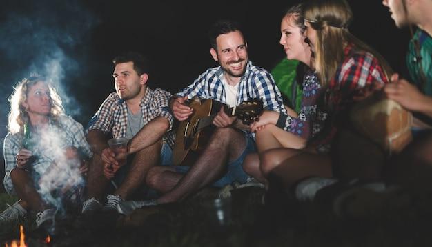 Счастливые друзья играют музыку и наслаждаются костром на природе