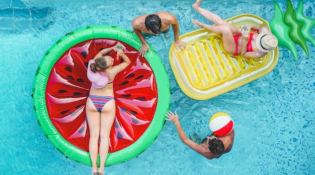 Счастливые друзья играют с воздушным шариком внутри бассейна