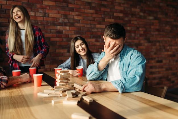 Счастливые друзья играют в настольную игру за столом в кафе