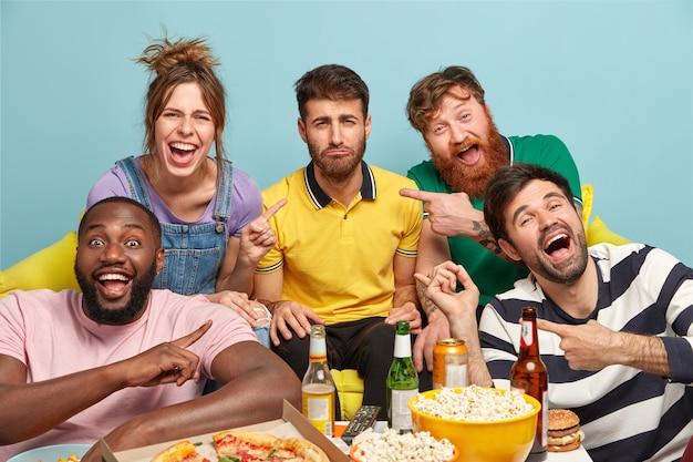 Gli amici felici indicano un ragazzo barbuto infelice che non è desideroso di guardare la commedia, esprime insoddisfazione. cinque giovani multietici fanno uno spuntino gustoso e bevono birra fredda mentre guardano la tv in streaming