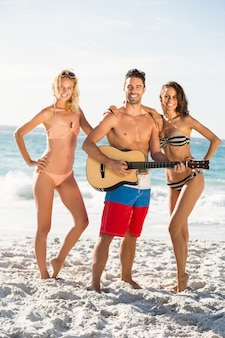 ビーチでポーズをとってギターを弾く幸せな友達