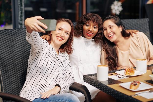 Selfieのポーズをとって幸せな友達