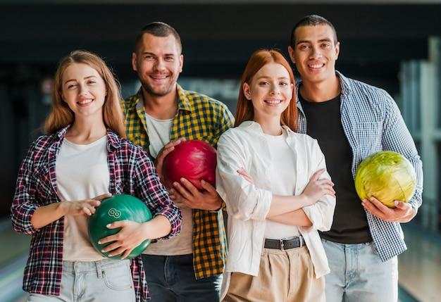 Счастливые друзья позируют в боулинг-клубе