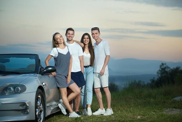 Happy friends posing near silver cabriolet.