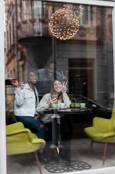 Amici felici che propongono attraverso la finestra