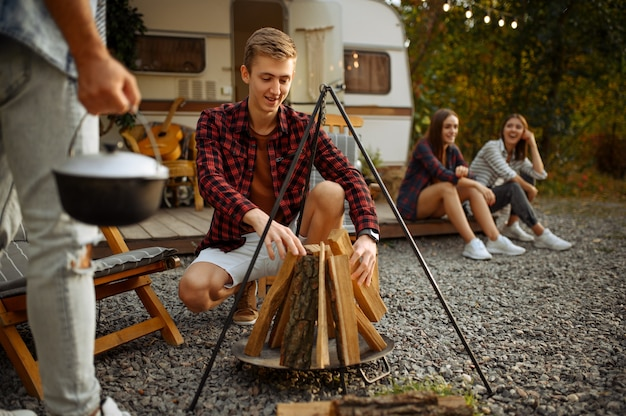 Happy friends prepares to cooking on campfire, picnic at camping in the forest. youth having summer adventure on rv, camping-car  two couples leisures, travelling with trailer