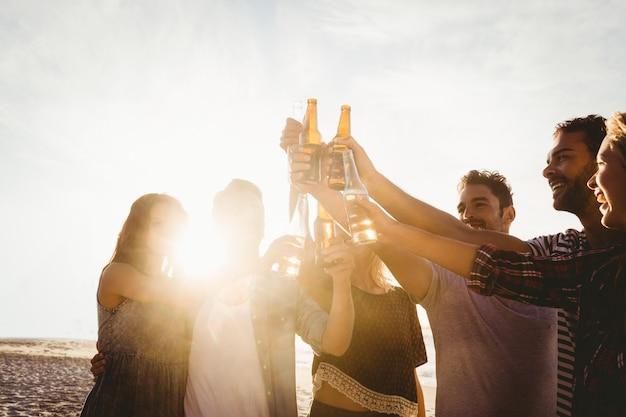 Happy friends raising beer bottles
