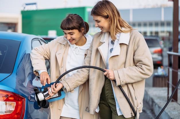 Gli amici felici fanno rifornimento di carburante alla stazione di servizio. viaggio di vacanza di amici