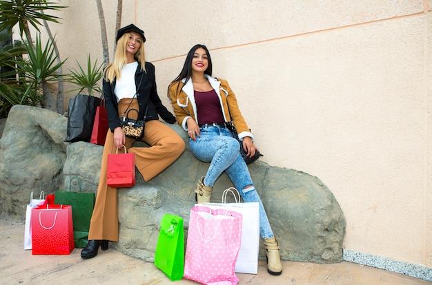 たくさんの買い物袋を持って買い物をした後、カメラに向かってポーズをとって休んでいる幸せな友達