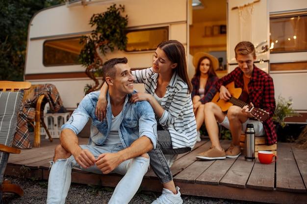 Счастливые друзья отдыхают возле автодом на пикнике в кемпинге в лесу. молодежь в летнем путешествии на автодоме, в машине для кемпинга две пары отдыхают, путешествуют с прицепом