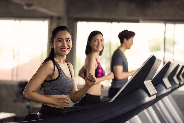 Happy friends run exercise on treadmills