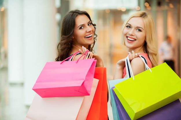 Счастливые друзья по магазинам. две красивые молодые женщины наслаждаются покупками в торговом центре