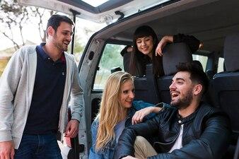 Happy friends sitting on car trunk