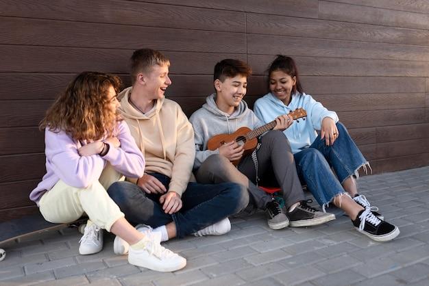 Happy friends sitting outdoors with ukulele