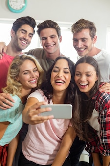 Happy friends smiling while taking selfie at home