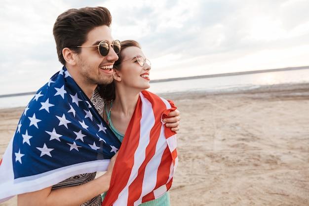 미국 국기를 들고 해변에서 시간을 보내는 행복 친구