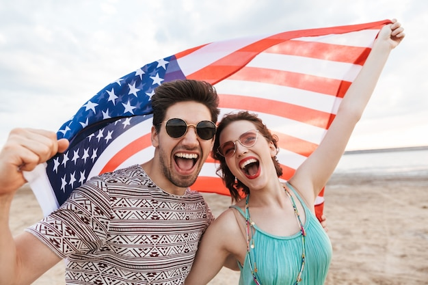 Happy friends spending time at the beach, holding american flag