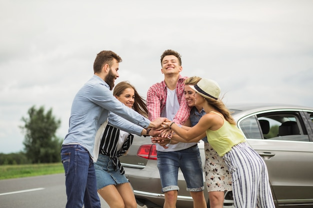 Happy friends stacking each other's hand standing near the car