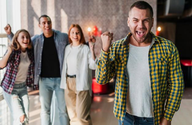 Happy friends standing in a bowling club medium shot