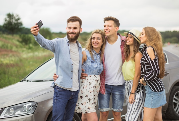Happy friends standing near the car taking selfie on cell phone