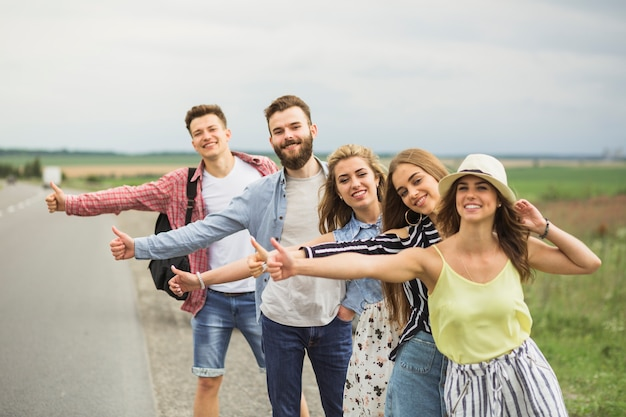 Happy friends standing in row on road hitchhiking