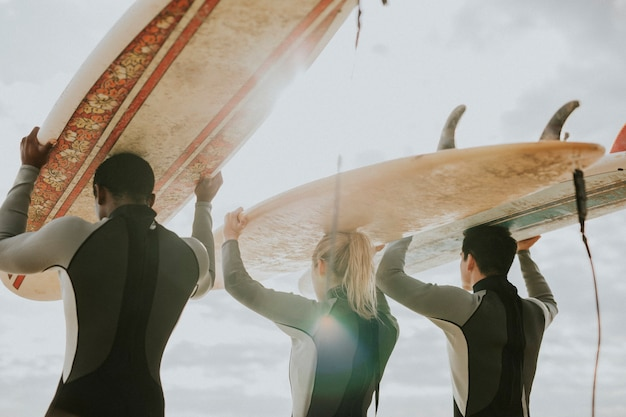 ビーチでサーフィンをしている幸せな友達