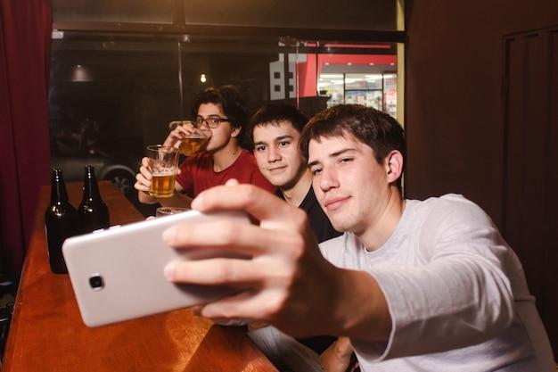 Счастливые друзья делают селфи, попивая пиво в баре.
