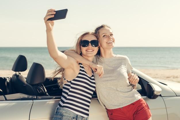 Happy friends taking selfie in car