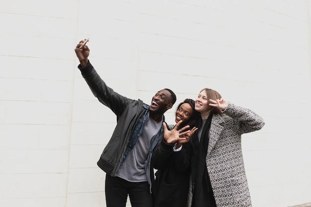 Amici felici che prendono lo spazio della copia del selfie