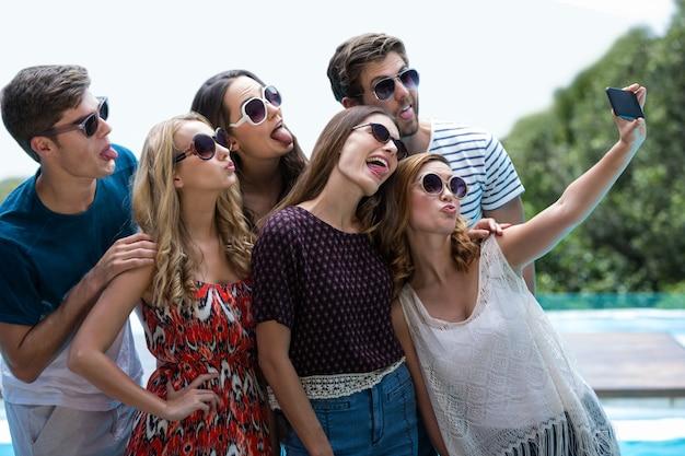 Happy friends taking a selfie near swimming pool
