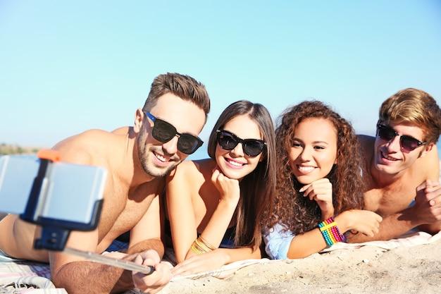 Счастливые друзья, делающие селфи на пляже