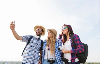Happy friends taking selfie on smartphone at outdoors