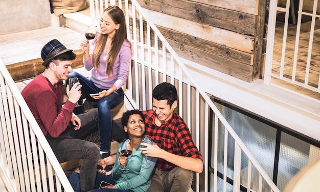 Счастливые друзья дегустируют красное вино и веселятся на лестнице