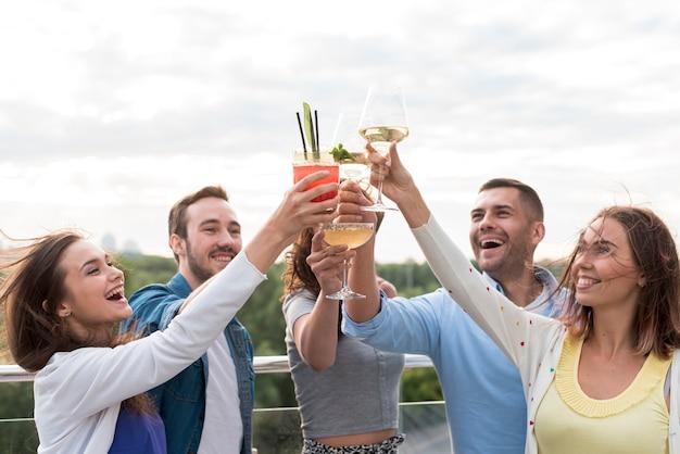 幸せな友達がパーティーで乾杯