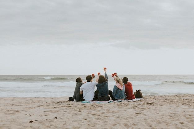 ビーチで乾杯する幸せな友達