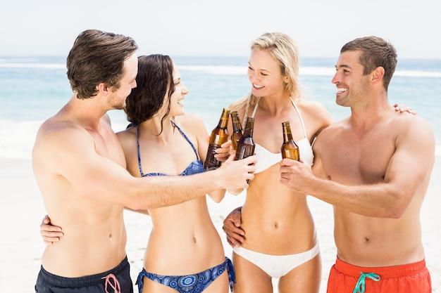 幸せな友達がビーチでビール瓶を乾杯