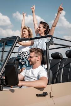 Amici felici che viaggiano in macchina insieme