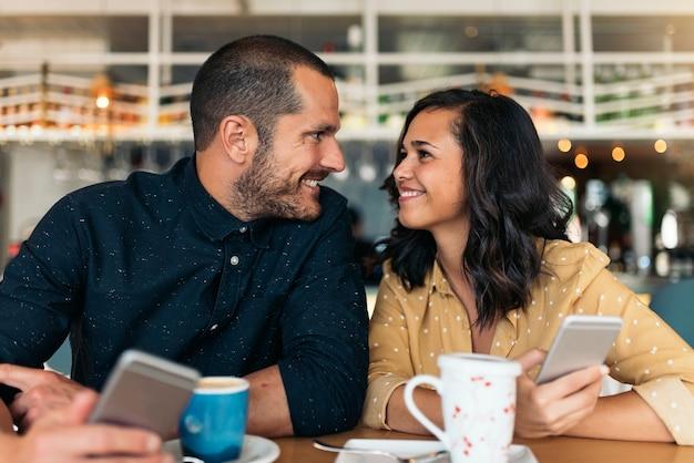 コーヒーショップでモバイルを使用して幸せな友達。