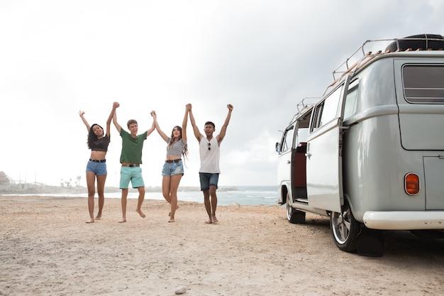 ビーチを歩いて幸せな友達と手を上げる