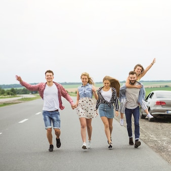 Happy friends walking on road together making fun