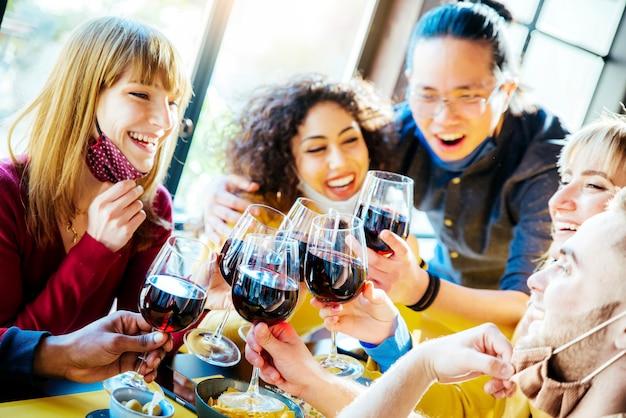 バーのレストランに座って赤ワインを乾杯する保護フェイスマスクを身に着けている幸せな友達