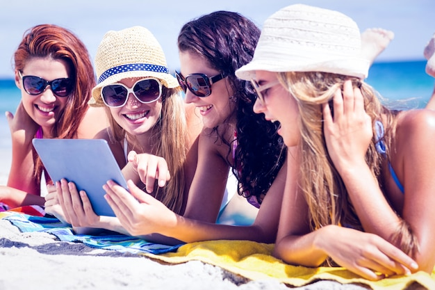 Happy friends wearing sunglasses and using tablet