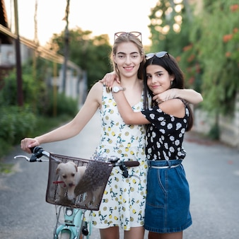 Happy friends with bicycle looking at the camera