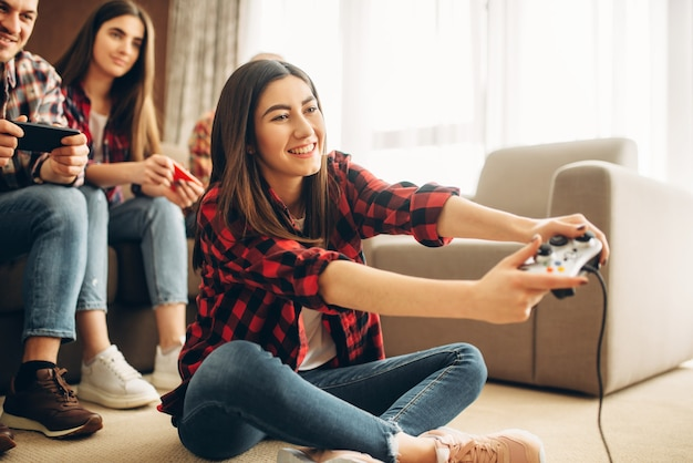 Happy friends with joysticks plays video console