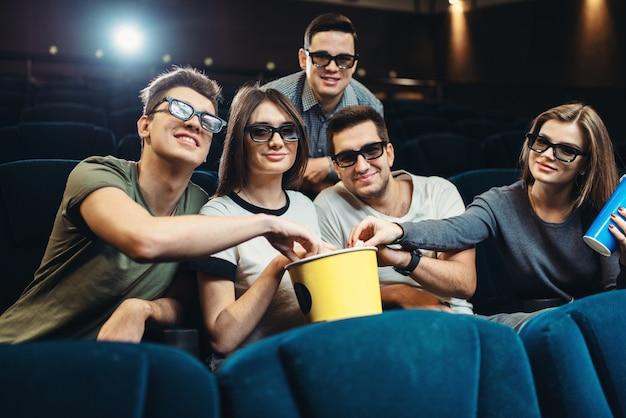 映画館で映画を見ているポップコーンと飲み物との幸せな友達。娯楽産業