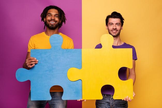 黄色の上に手にパズルを持つ幸せな友達。統合、結合、パートナーシップの概念