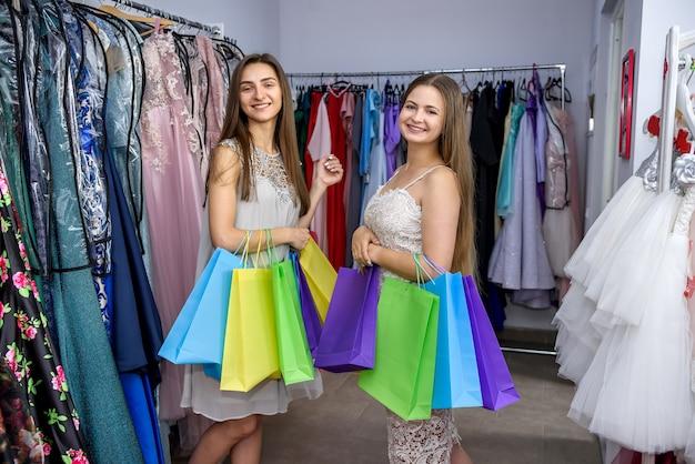 Счастливые друзья с сумками в магазине одежды
