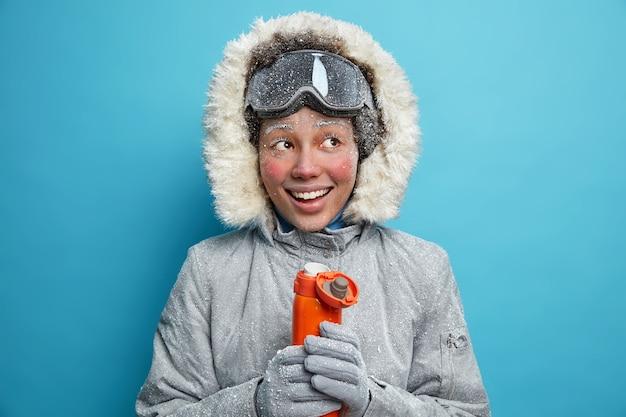 겨울 옷을 입은 행복한 서리가 내린 여자는 추운 날씨에 따뜻해지며 보온병 미소에서 따뜻한 차를 마시 며 스키 고글을 착용하고 활동적인 휴식을 취합니다. 용감한 긍정적 인 여성 등산객.